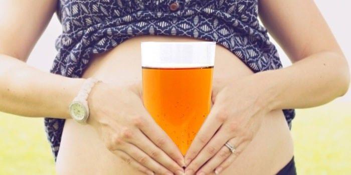 Беременная девушка с бокалом пива
