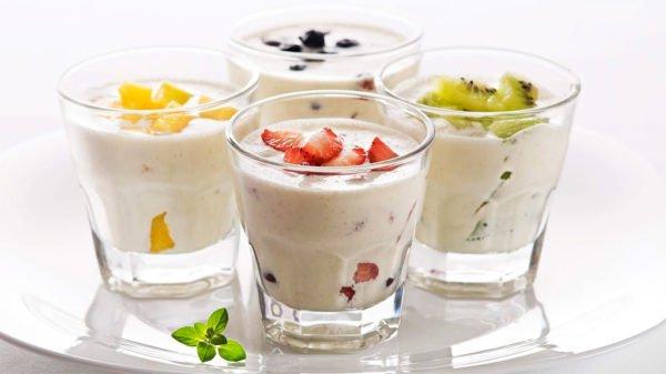Стаканы, наполненные кисломолочными продуктами и украшенные фруктами