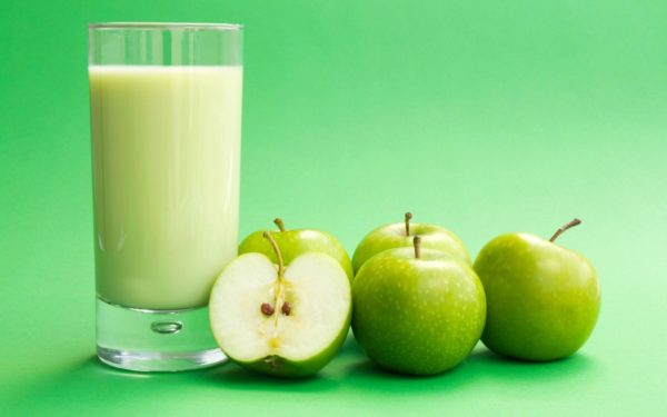 Яблоки и кефир в стакане на зелёном фоне